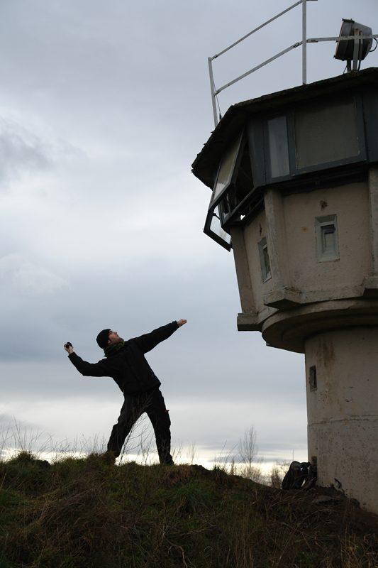 Pierre gegen Wachturm an der früheren deutsch-deutschen Grenze bei Helmstedt