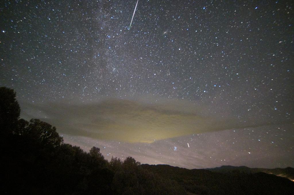 Milchstraße, die Plejaden (der Sternhaufen unterhalb der Wolke) und Andromeda (oben, rechts neben dem Meteorstreifen)