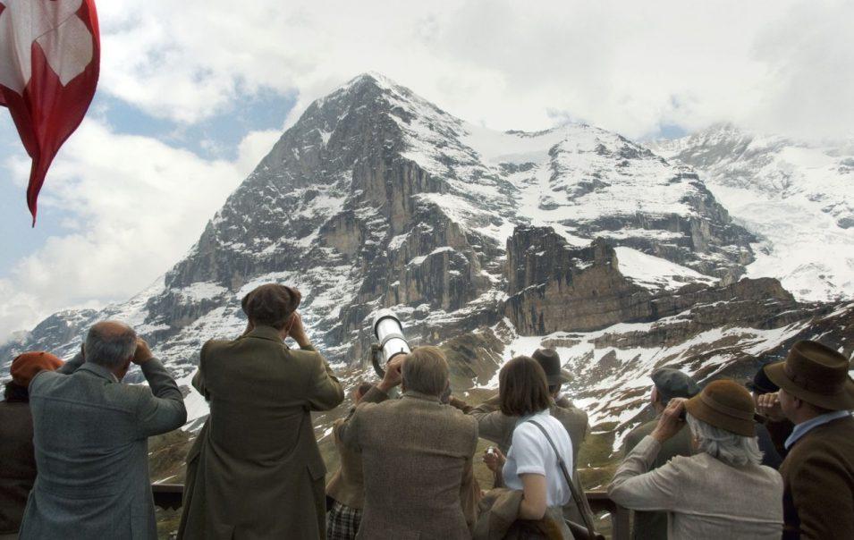 Schaulustige beobachten den Aufstieg der Bergsteiger mit Fernrohren