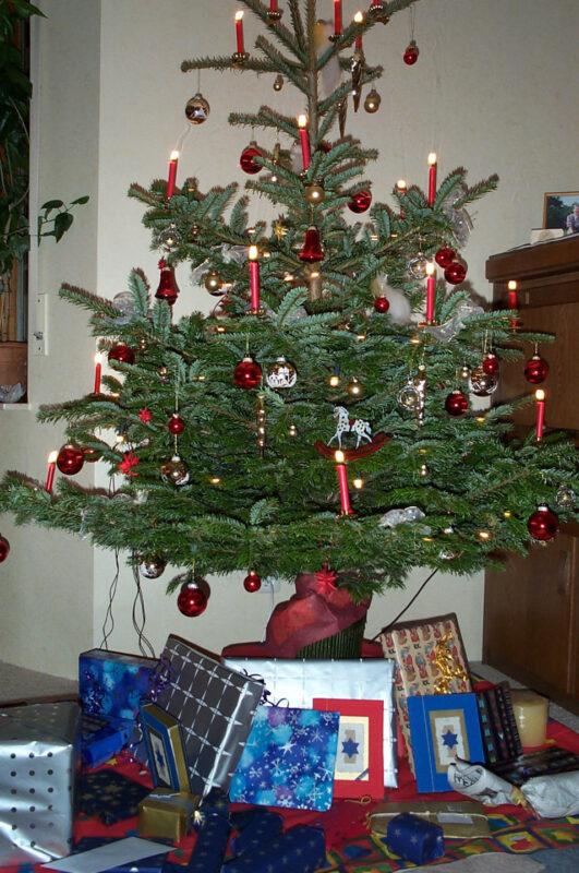 Geschmückter Weihnachtsbaum mit roten Kerzen und roten und goldenen Glaskugeln