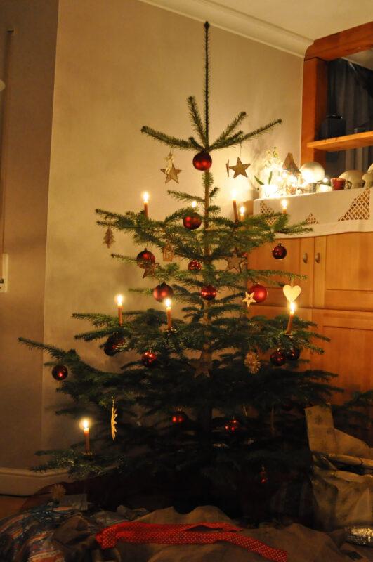 Leuchtender Weihnachtsbaum mit gelben Kerzen und roten Kugeln